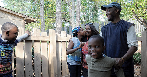 John, far right, has his hands full with his children, Miles, Meonah and Matthew. But the family is close and happy, and they all work together to make the home work. Youth Villages Family Intervention Specialist Kimberly Hardy is also pictured.