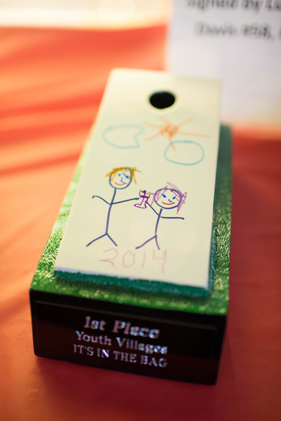 Winners of the cornhole tournament take home trophies designed by Youth Villages children.